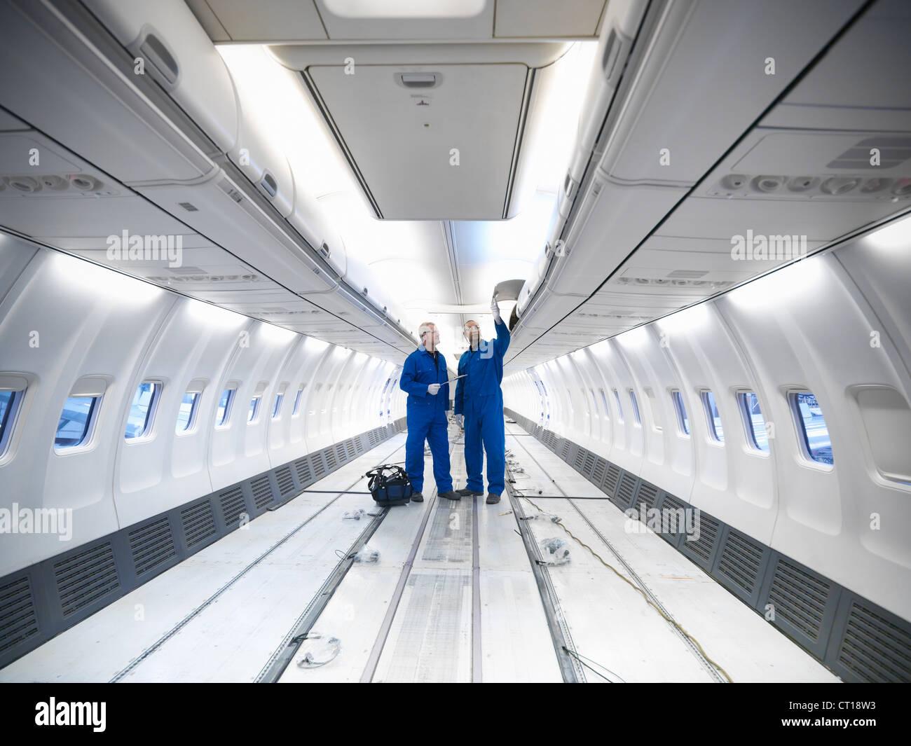 Worker examining empty airplane - Stock Image
