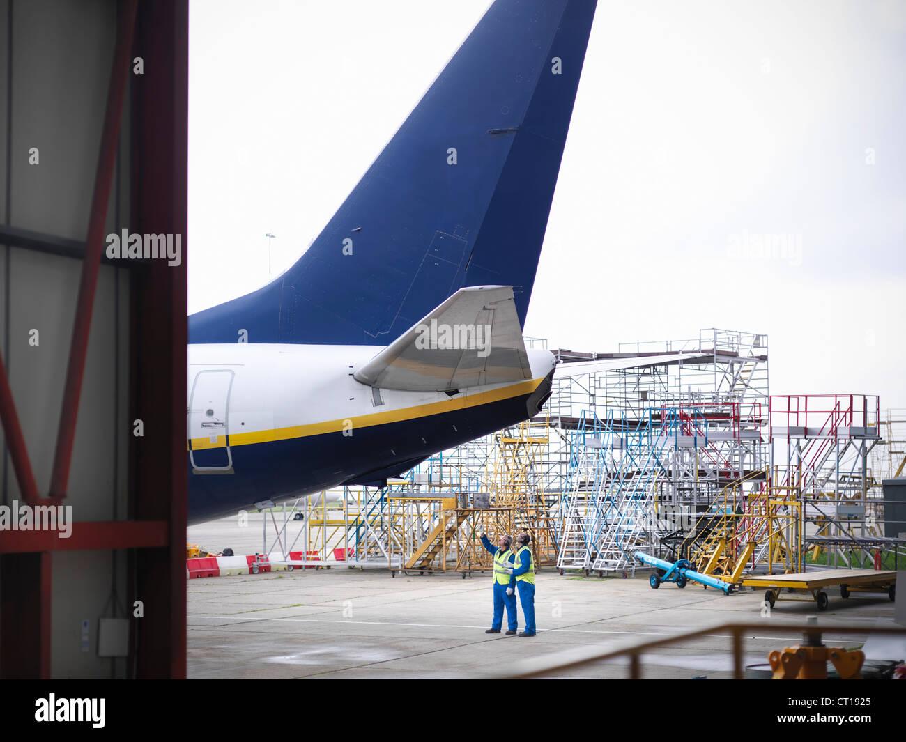 Workers examining underside of airplane - Stock Image
