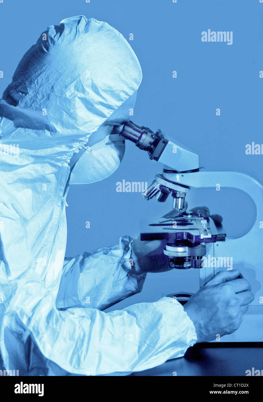 scientist at a microscope - Stock Image