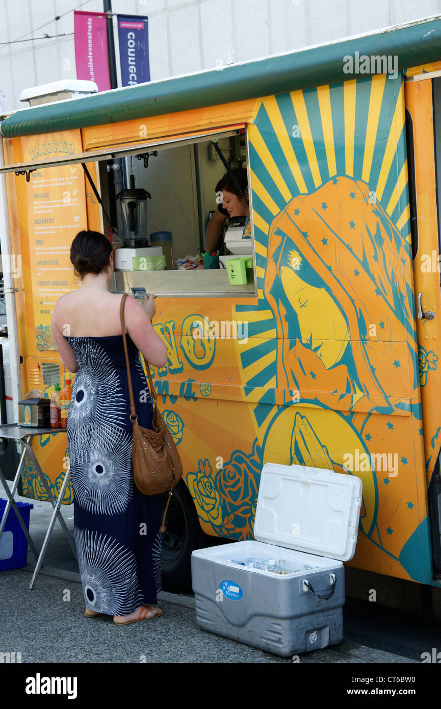 Young woman buying lunch at a Mexican street food truck in downtown Vancouver, British Columbia, Canada - Stock Image