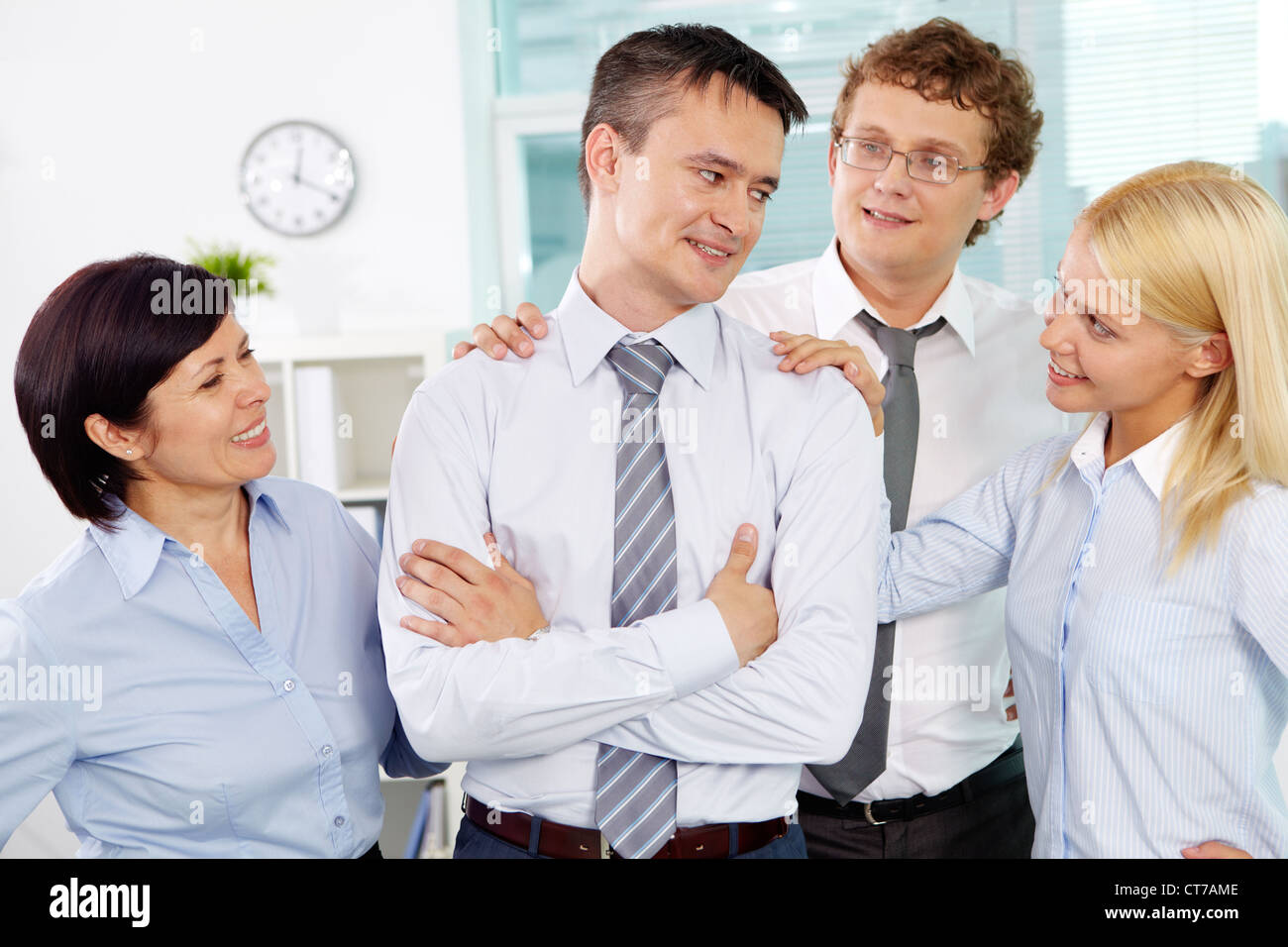 Group of friendly businesspeople adoring their leader in office - Stock Image
