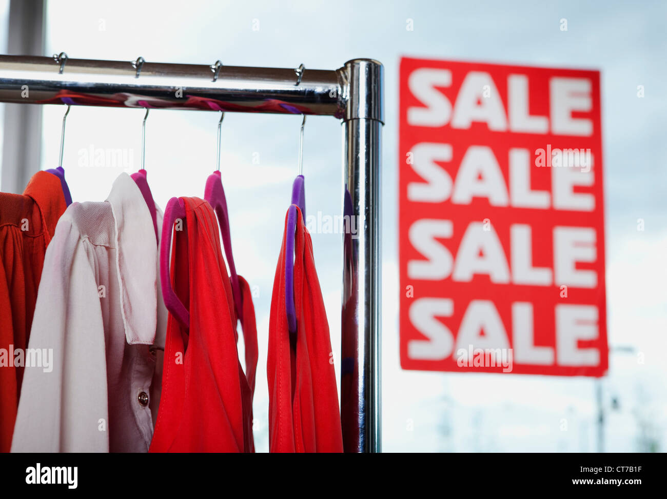Blouses in sale on clothes rail - Stock Image