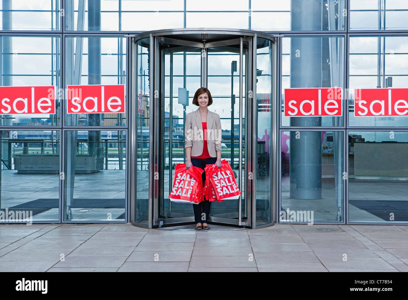 Woman in shop doorway with sale bags - Stock Image