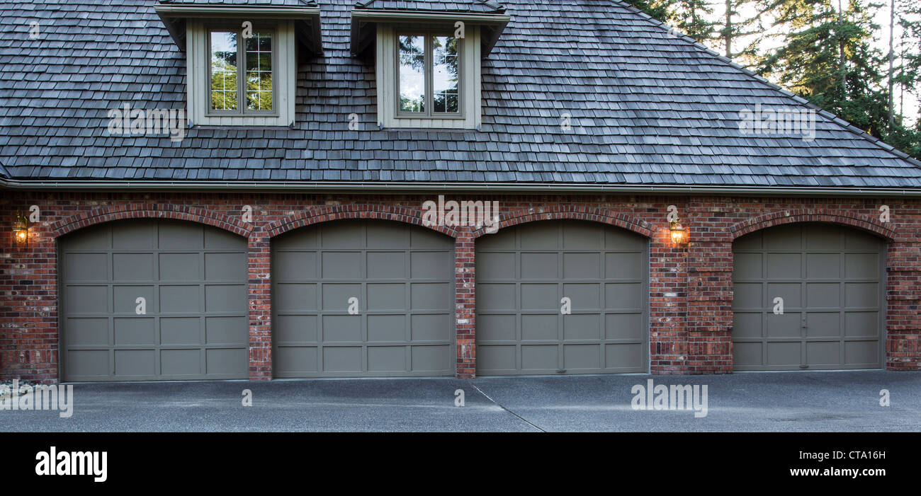 Four Car Garage Doors Made Of Wood And Brick With Trees And Sky In