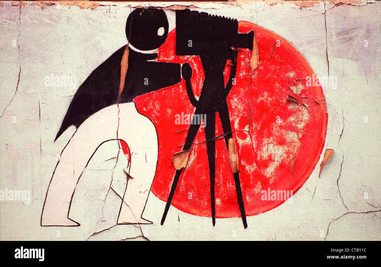 An art deco illustration of a photographer with camera and tripod decorates the wall of an abandoned building in - Stock Image