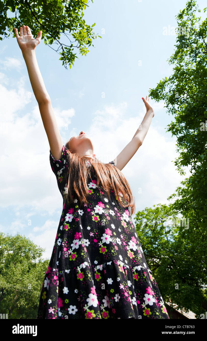Teen girl with raised hands against blue cloudy sky - Stock Image