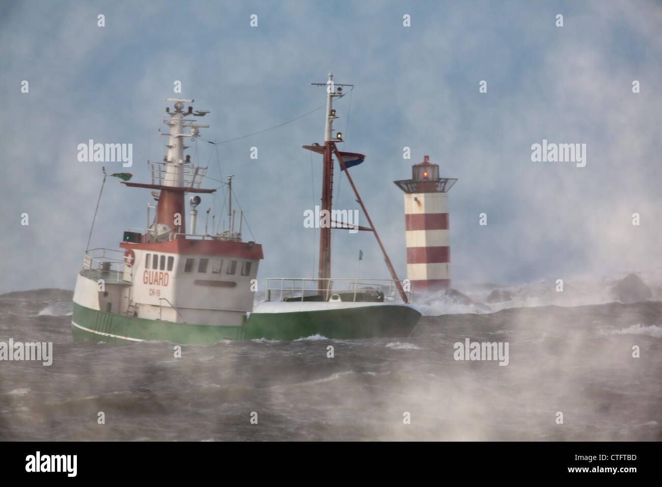 The Netherlands, IJmuiden, Storm. Waves smash against lighthouse or beacon. Ship. - Stock Image