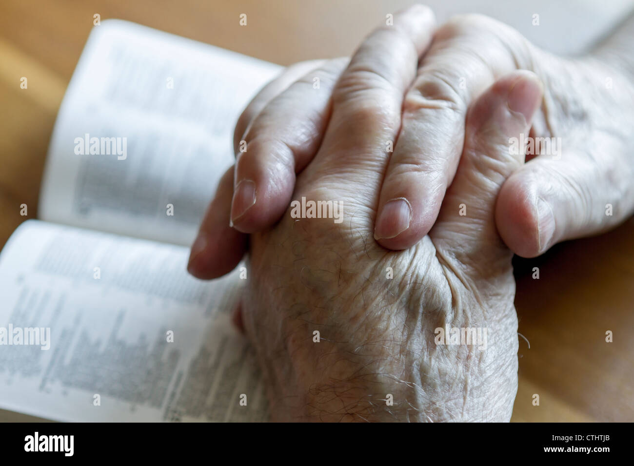 weathered old man's hands clasped in prayer over open Bible - Stock Image