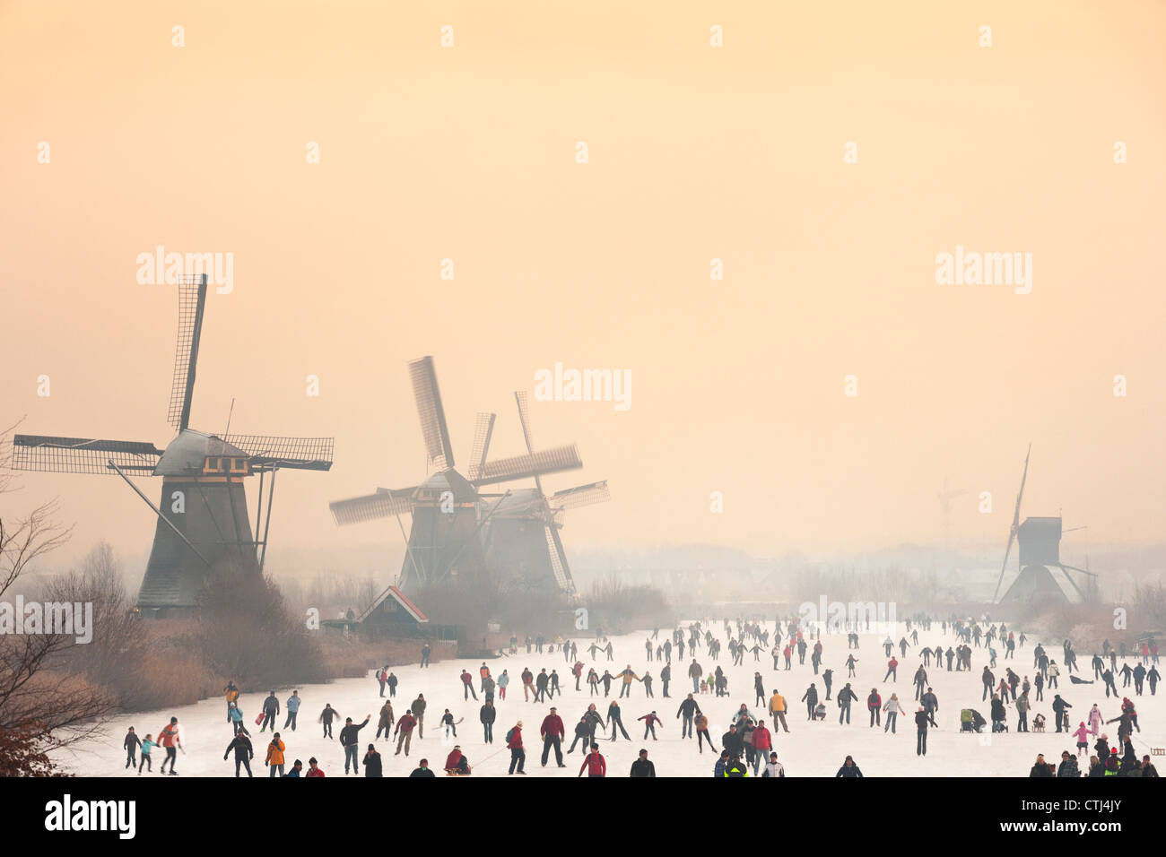 Dutch ice skaters in front of five of the 19 windmills at Kinderdijk in the Alblasserwaard polder, Holland, The Stock Photo