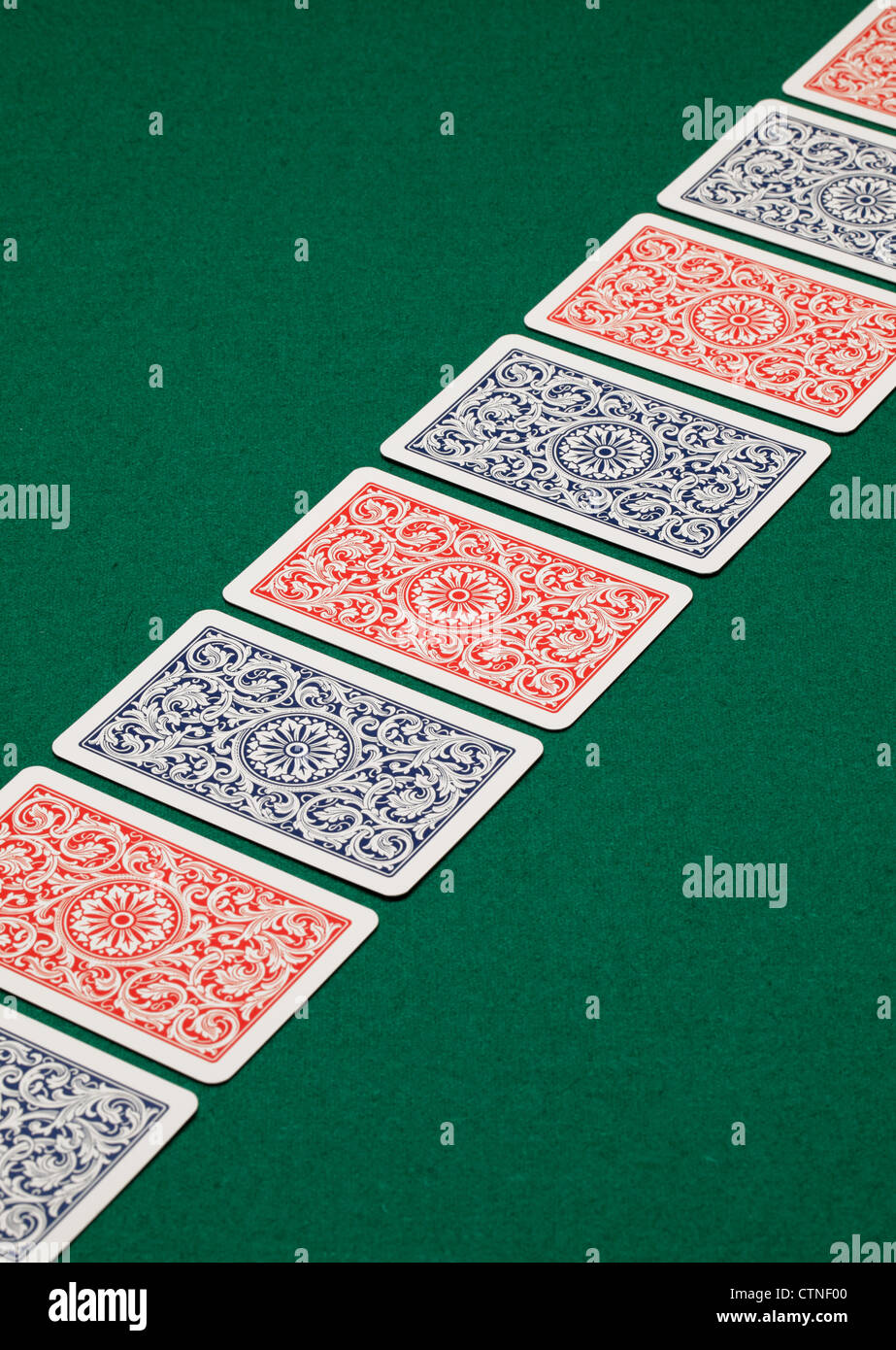 A diagonal line of playing cards on a green table. - Stock Image