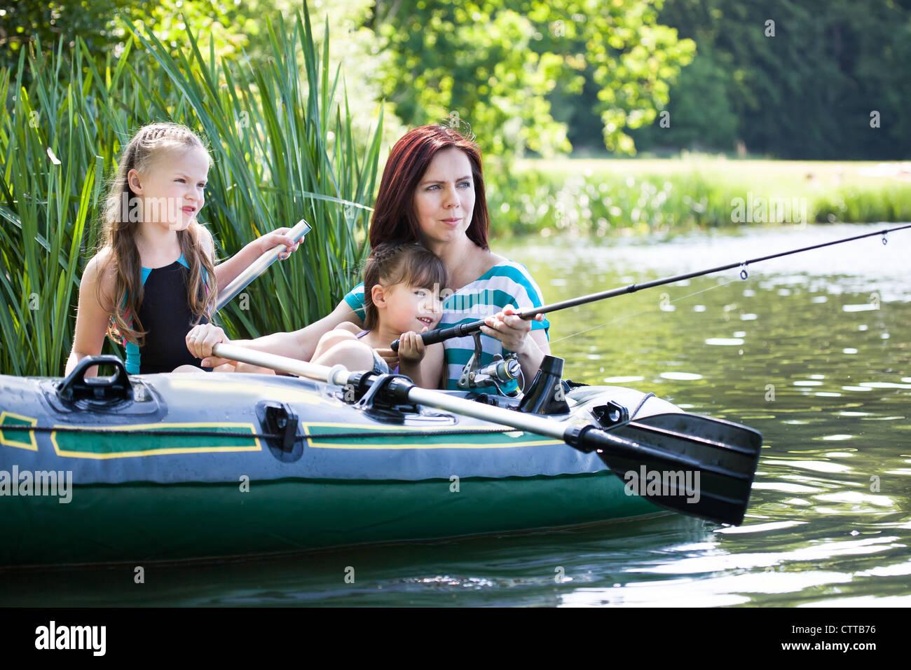 family fishing on lake at summer - Stock Image