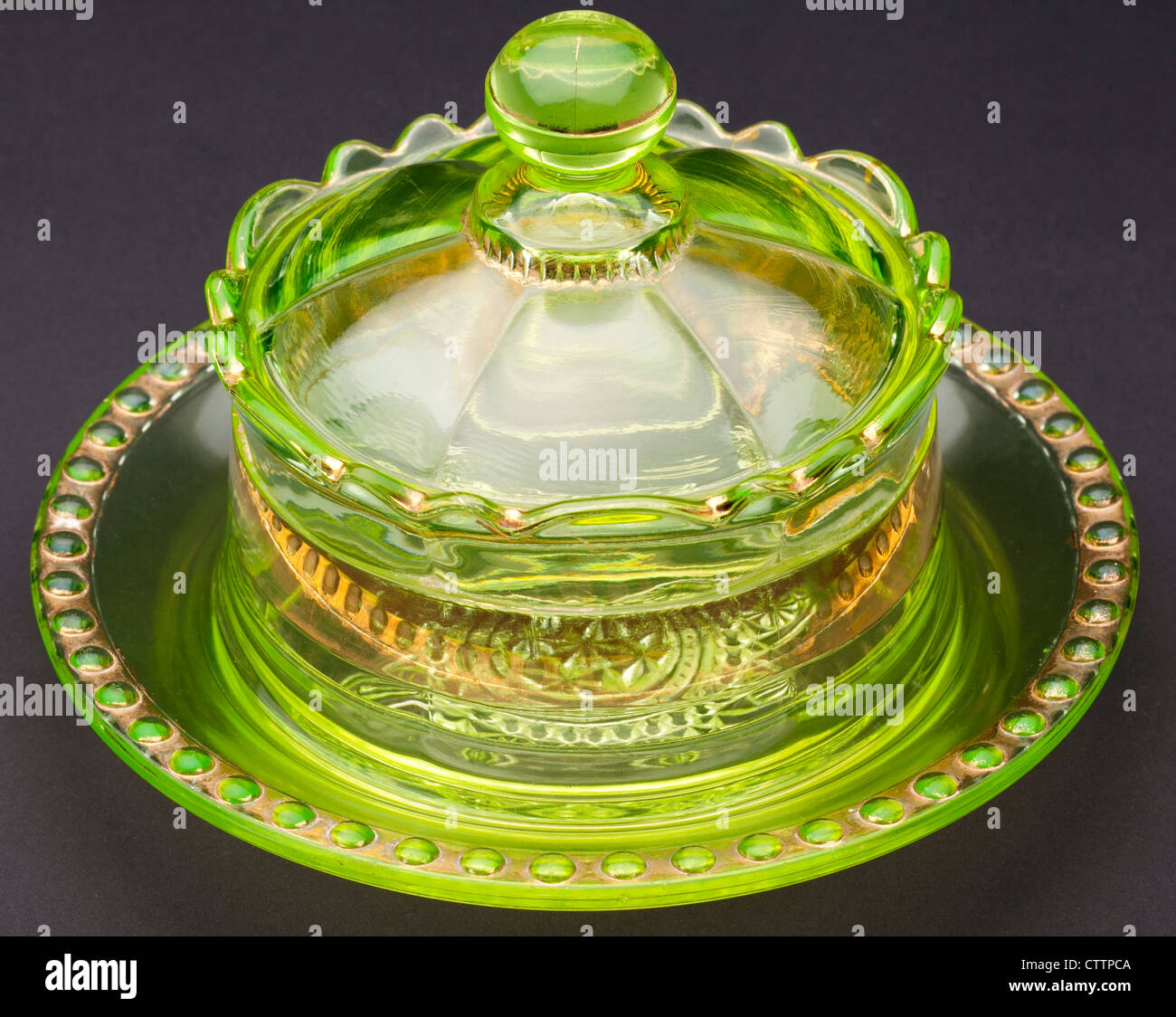 Top view of a Ranson 'gold band' Vaseline 'uranium glass' round covered butter dish produced by - Stock Image