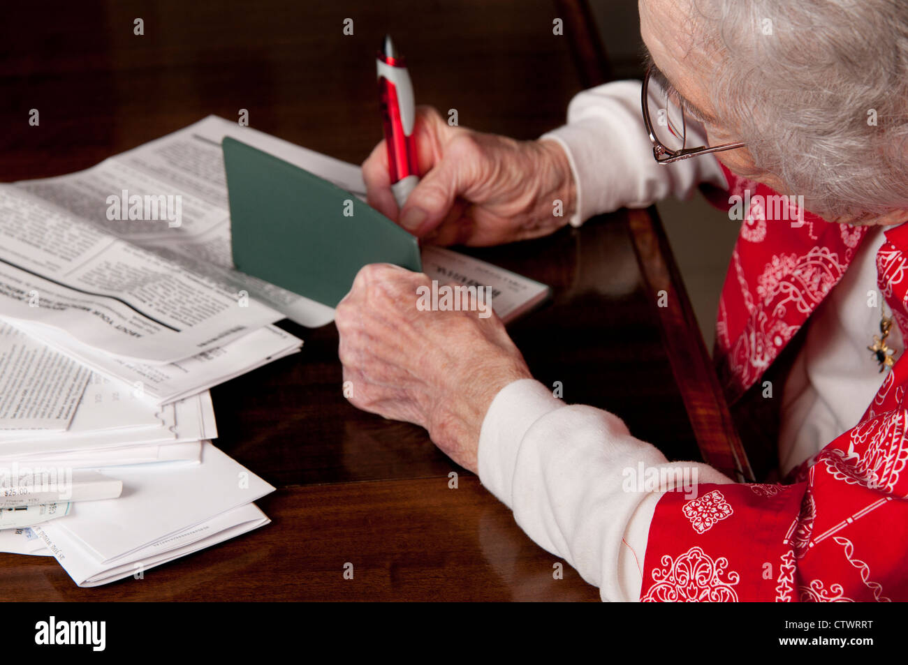 Elderly woman writing a check and paying personal finance bills - Stock Image