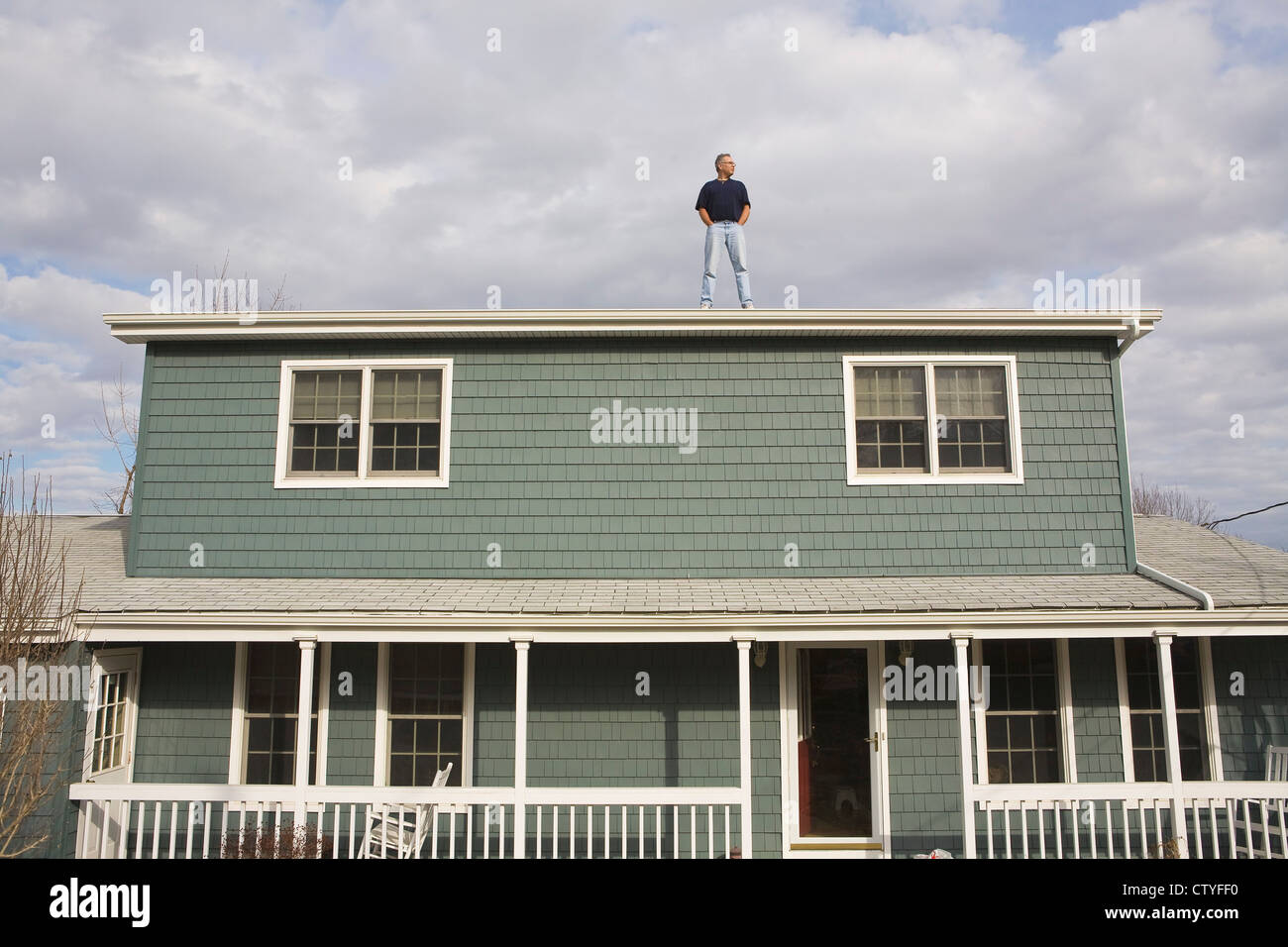 Man on Roof of Home - Stock Image