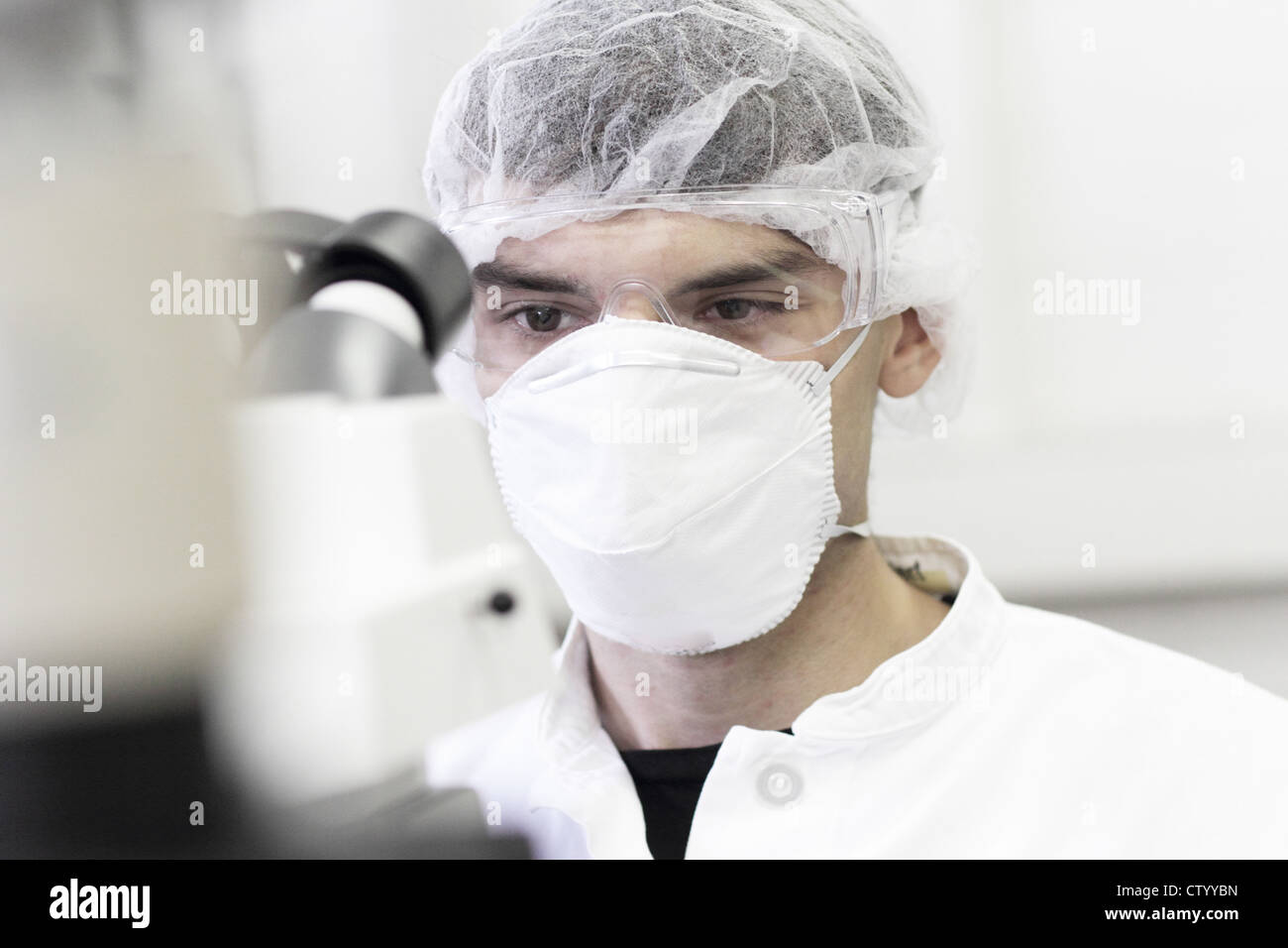 Scientist wearing facemask in lab - Stock Image