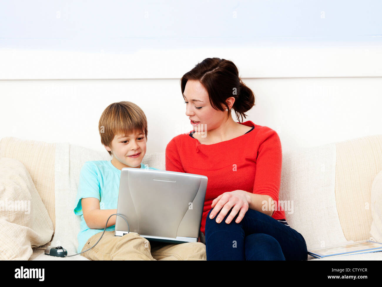 Mother and son using laptop together - Stock Image