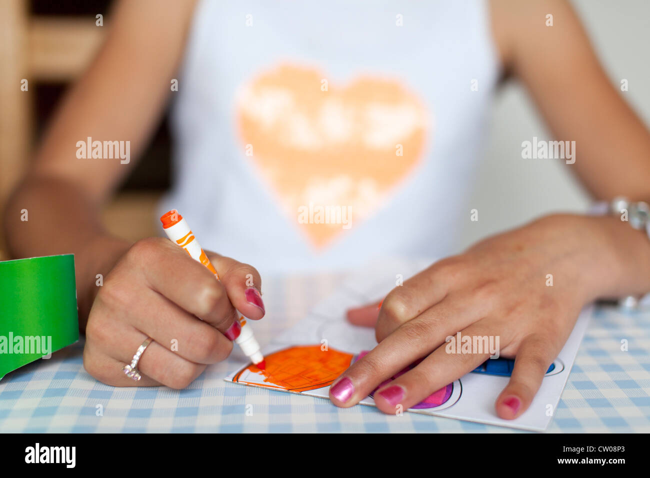 Young girl colouring in a picture. - Stock Image