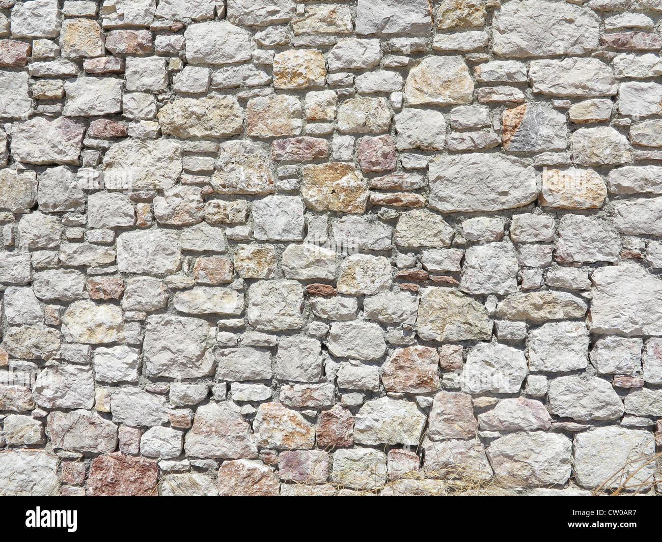 block stone wall made from irregular sized stone blocks stock photo