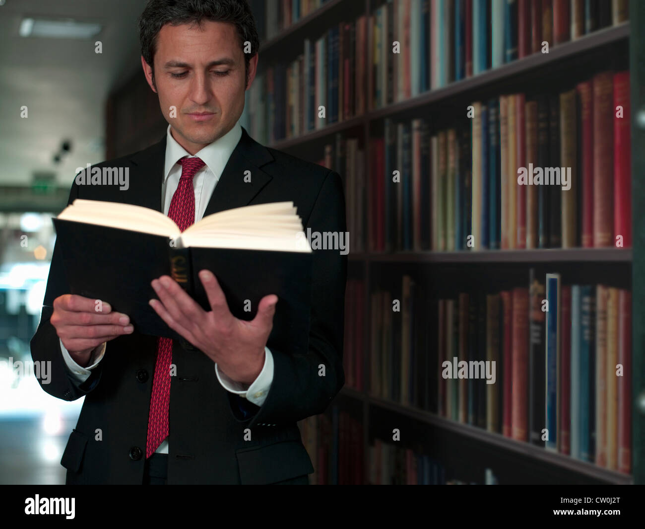 Businessman reading book in library - Stock Image