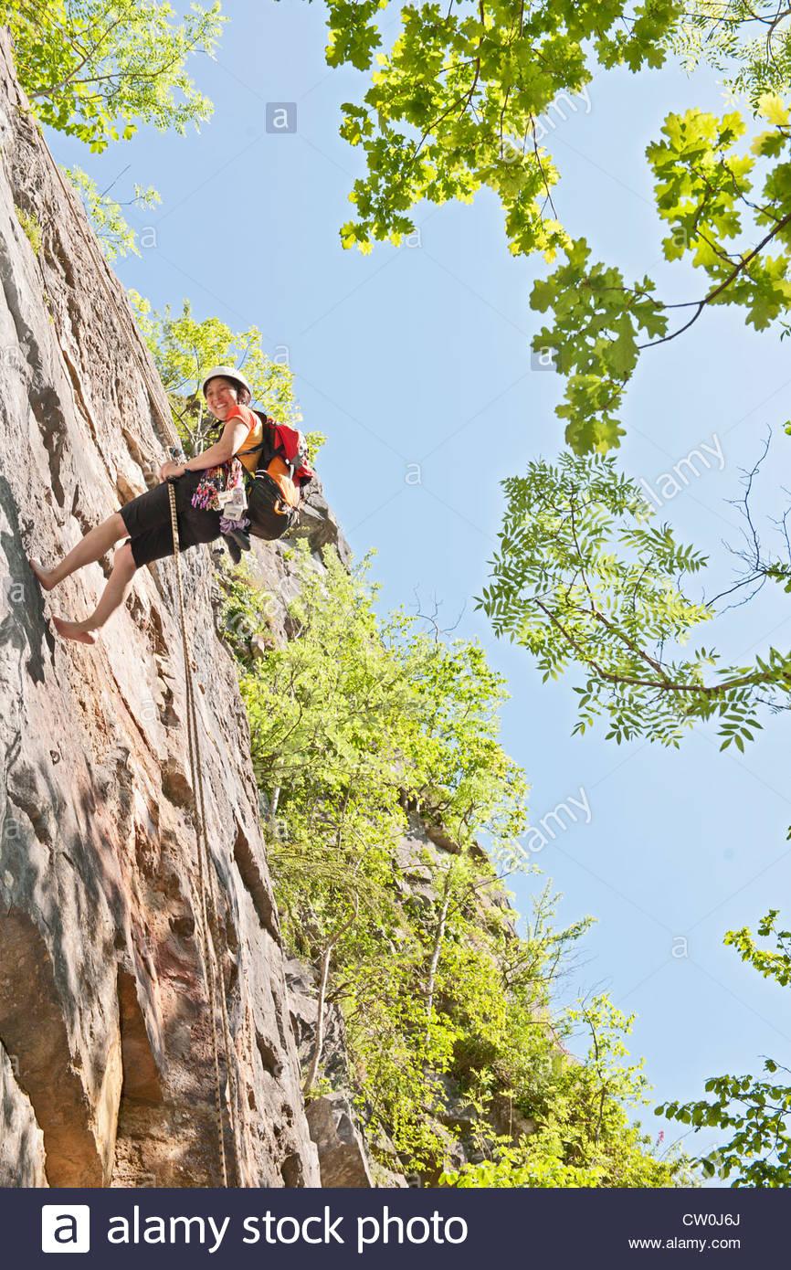 Climber scaling steep rock face - Stock Image