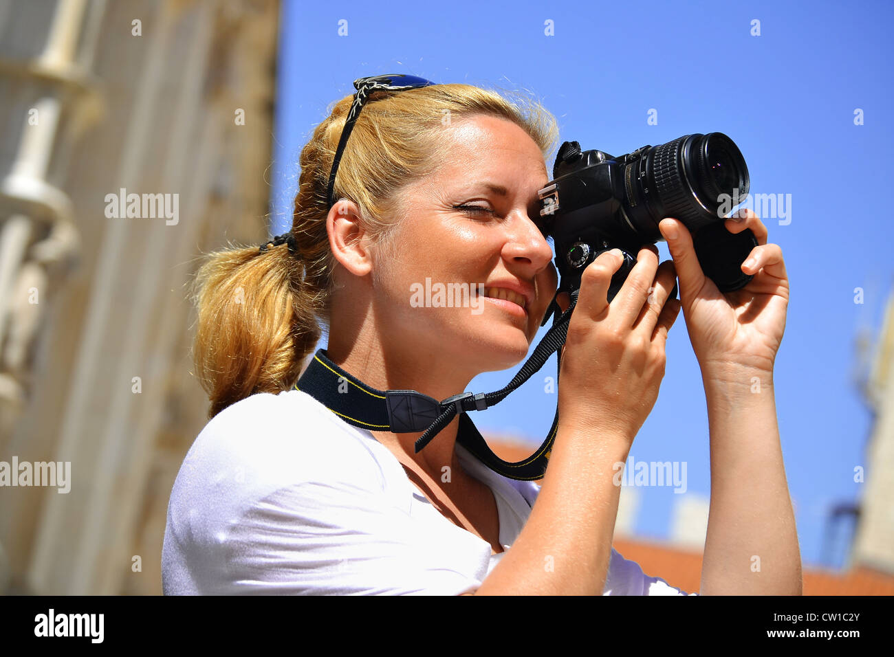 Young female tourist visiting Mediterranean old town on vacation. Woman taking photos on the street - Stock Image