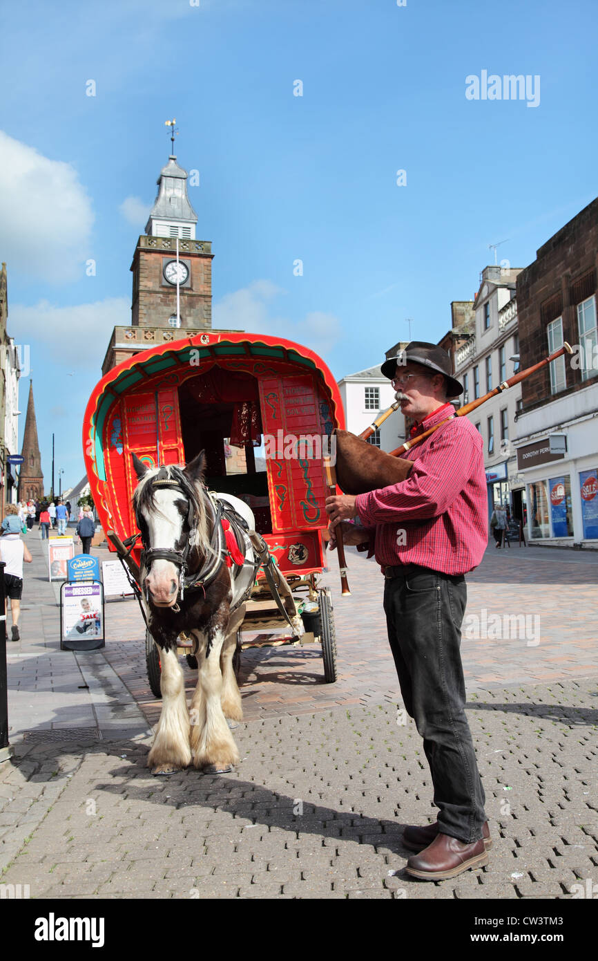 man-playing-pipes-in-front-of-gypsy-style-horse-drawn-caravan-at-dumfries-CW3TM3.jpg