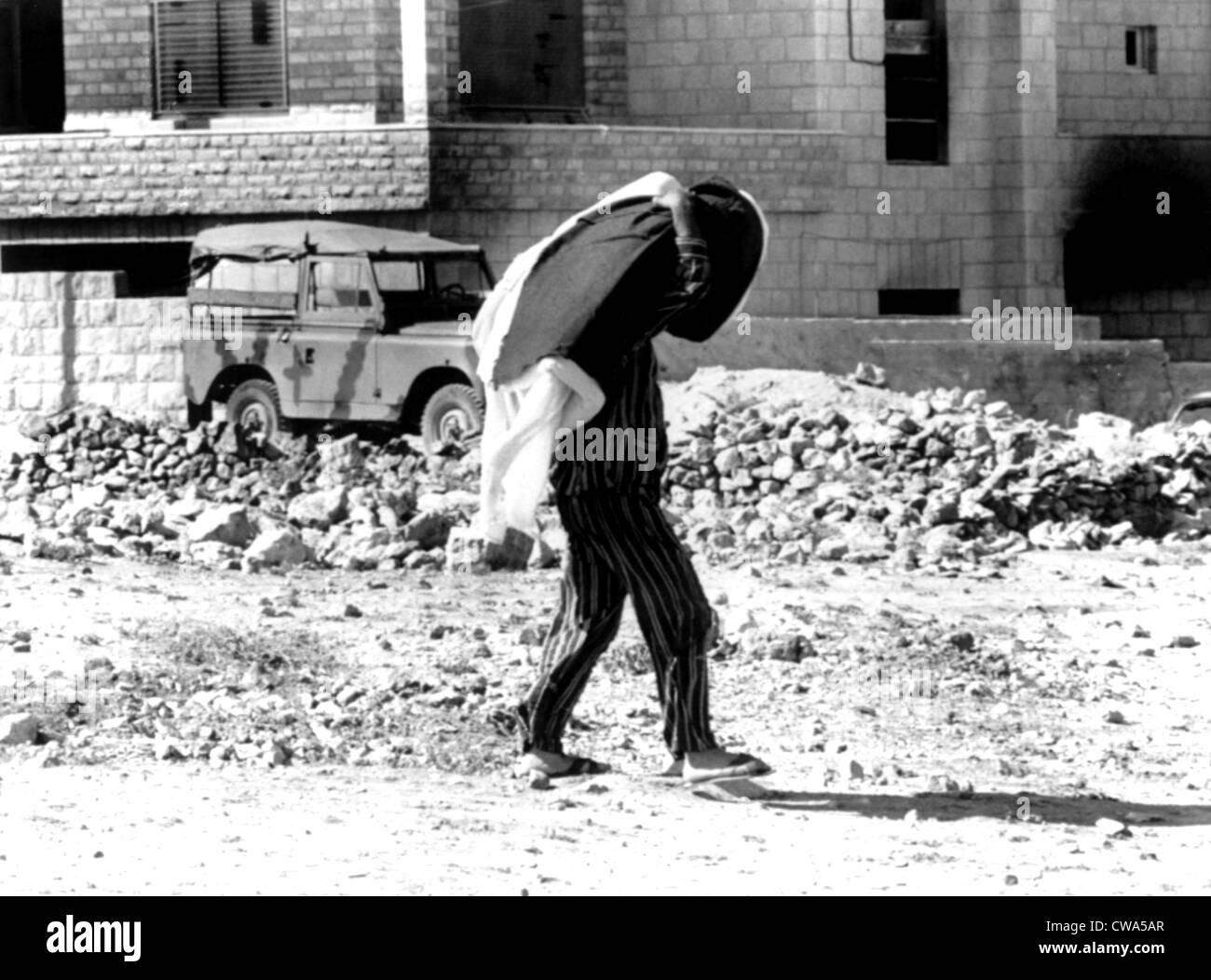 Arab-Israeli War, Jordanian in pajamas (carrying mattress & blankets) walking through war-torn city of Amman, - Stock Image