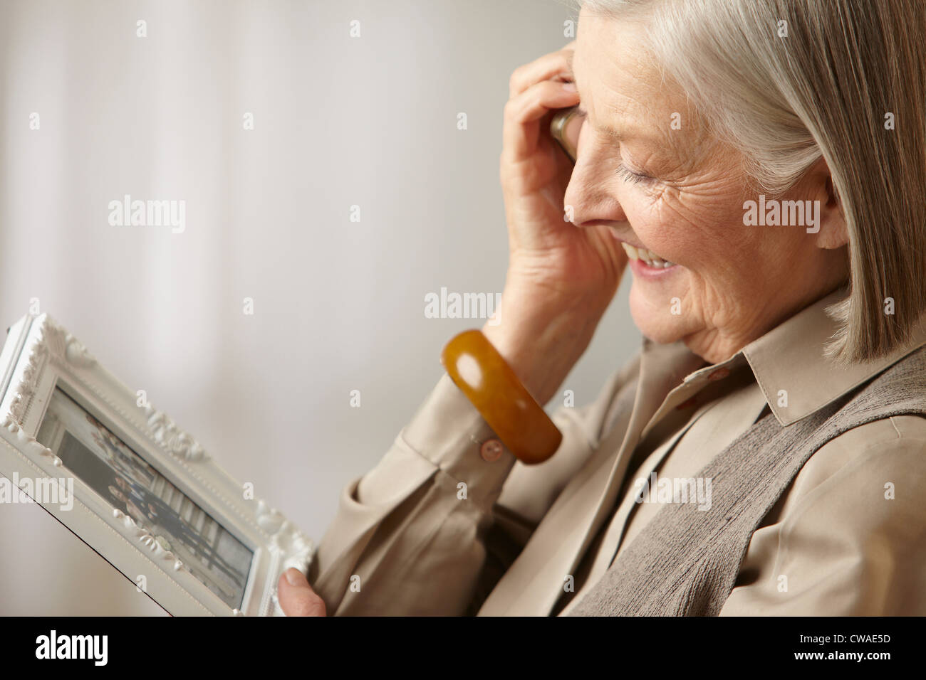 Senior woman holding picture frame - Stock Image