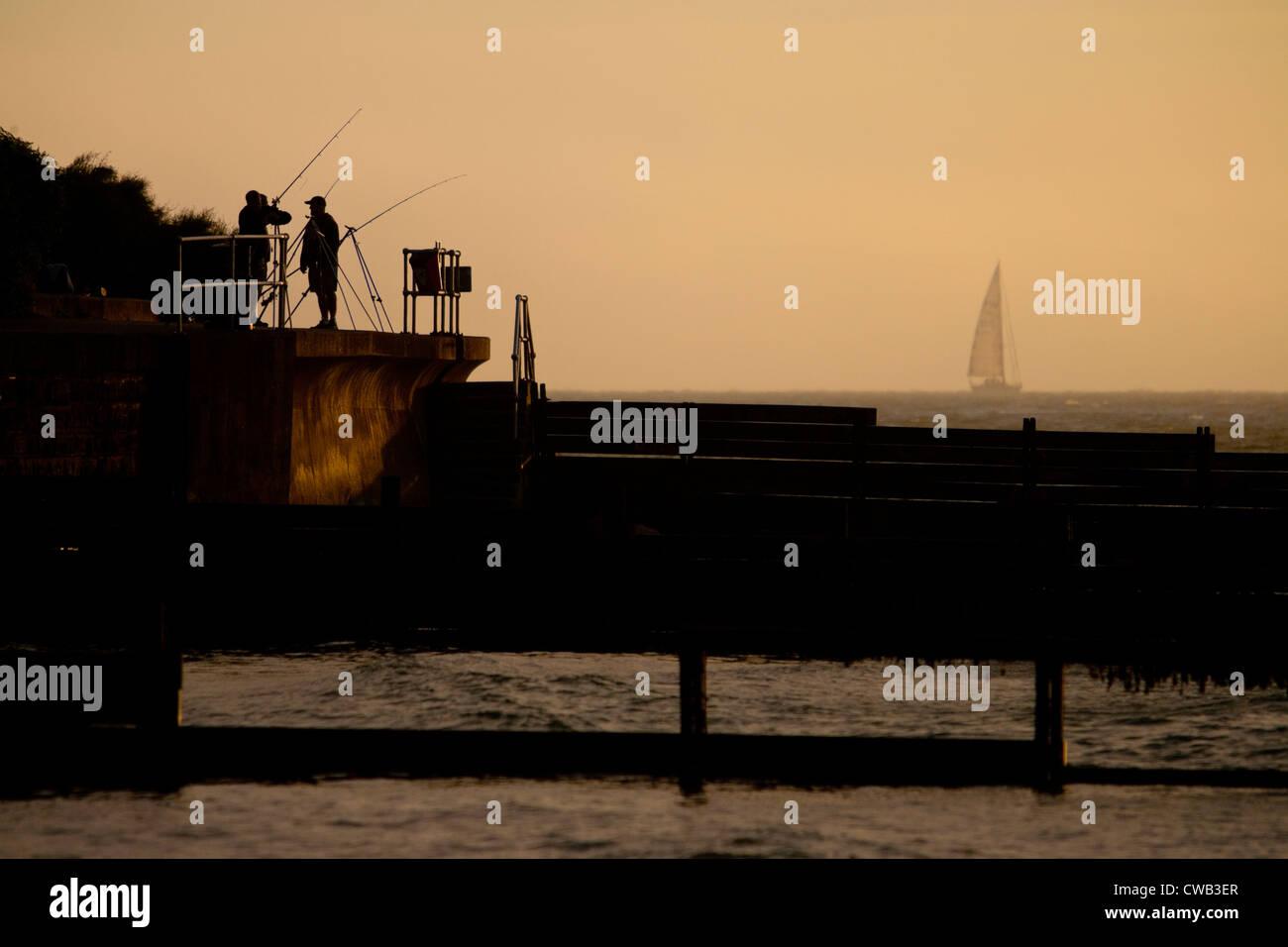 Angling, Fishing, Fishermen, Seawall, groynes, yacht, mist, Colwell Bay, Isle of Wight, England, UK, - Stock Image