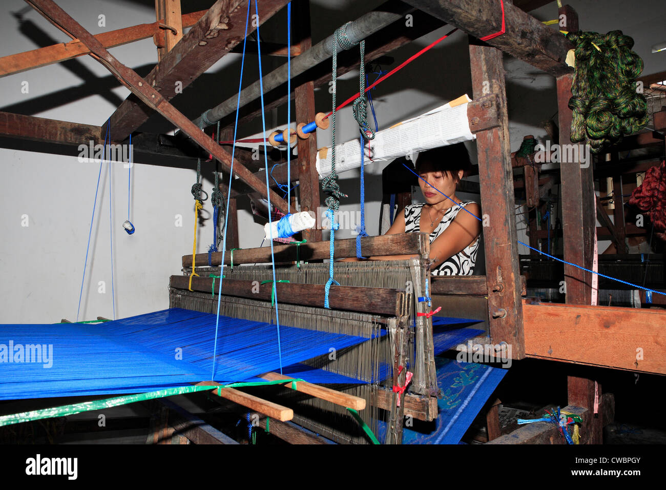 a-process-of-ikat-fabric-weaving-weaving-on-a-footloom-CWBPGY.jpg
