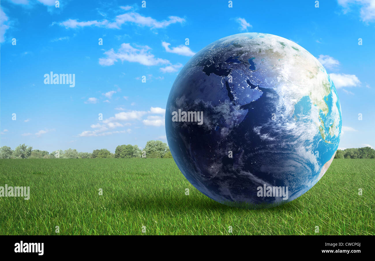 Earth globe on a green field of grass - Stock Image
