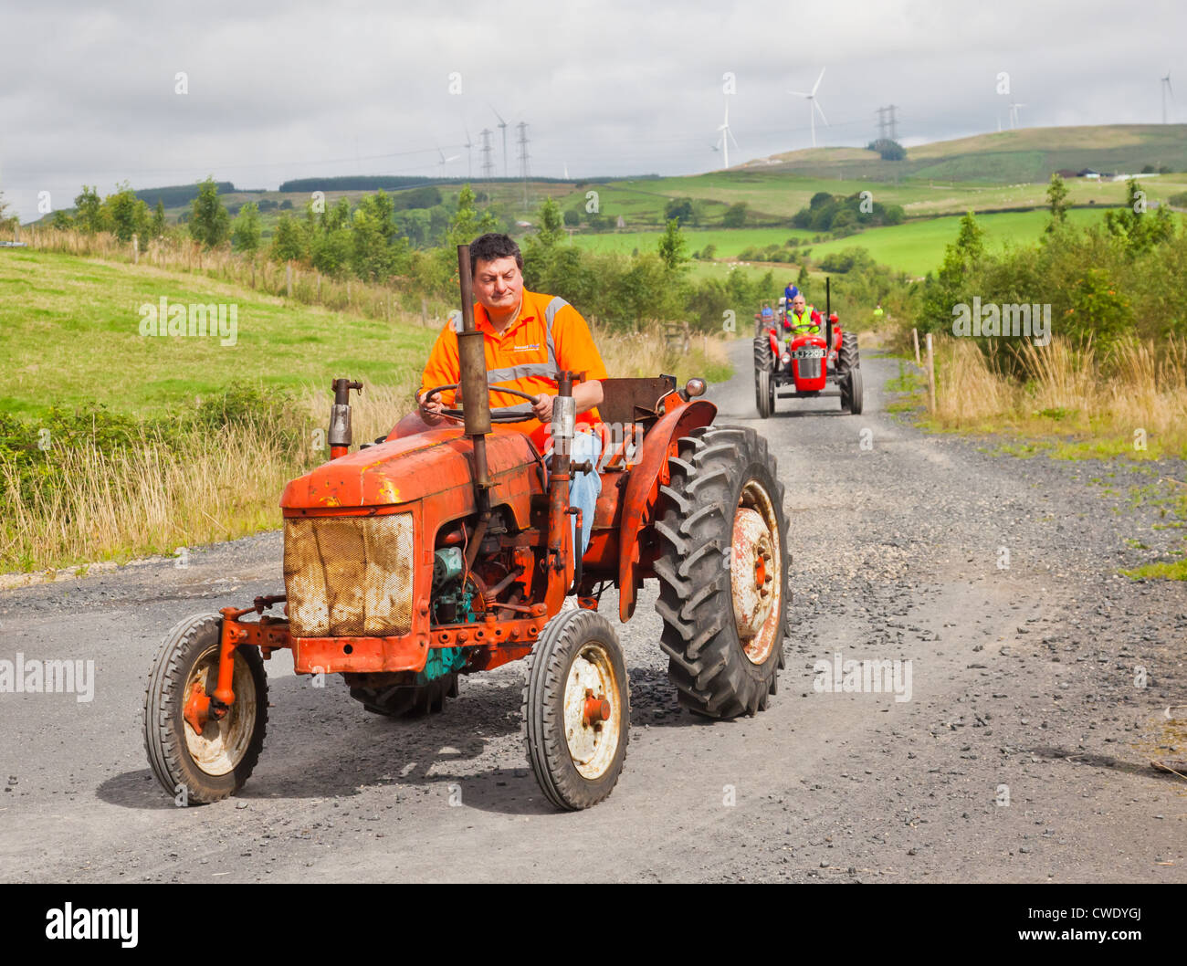Enthusiast driving an orange vintage BMC Mini tractor during an Ayrshire Vintage Tractor and Machine Club road run - Stock Image
