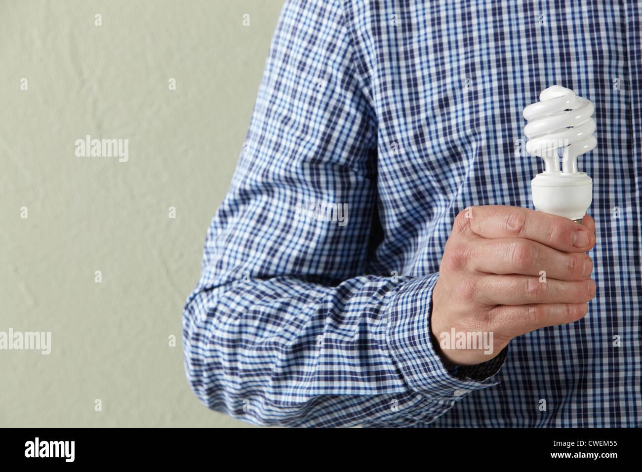 Cropped Studio Shot Of Man Holding Energy Saving Lightbulb - Stock Image