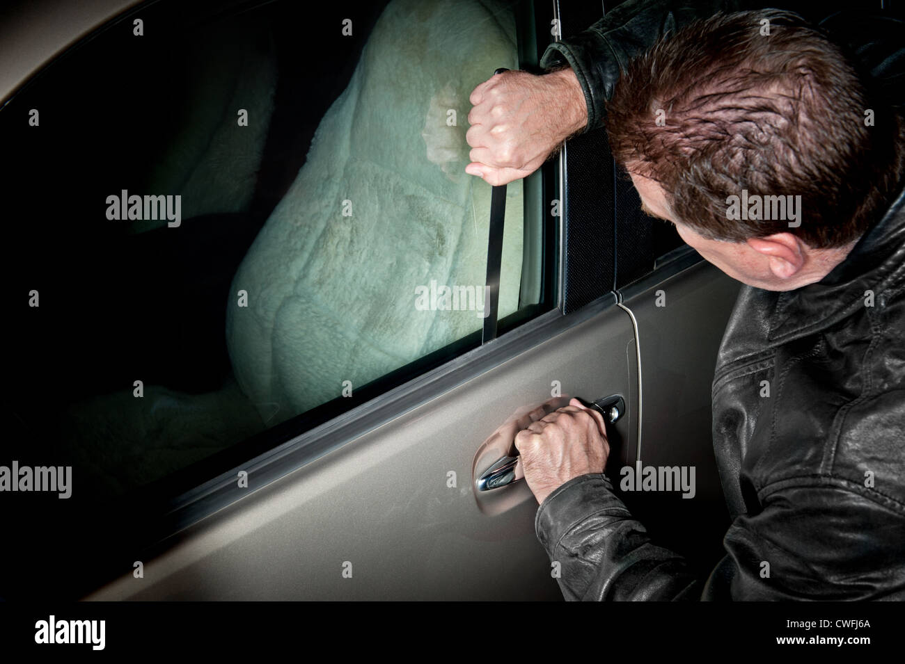 A male car thief uses a flat metal lock pick to break into a vehicle. Stock Photo