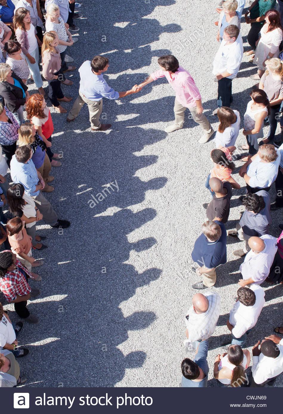 Men handshaking between separate groups - Stock Image