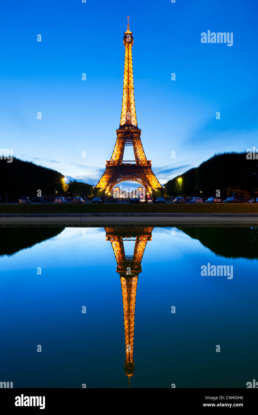 Paris Eiffel tower illuminated at night from the Champs de Mars gardens reflected in a pool Paris France EU Europe - Stock Image