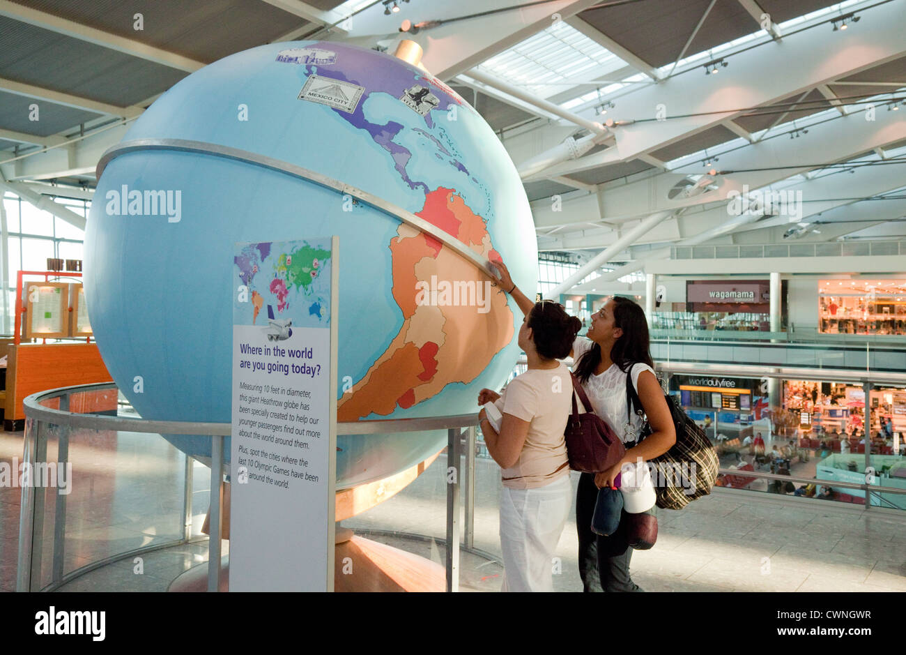 Young women looking at a large globe, Departure lounge, terminal 5, Heathrow airport London UK - Stock Image