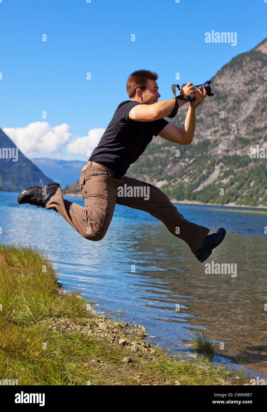 Young photographer shooting nature in the jump. - Stock Image