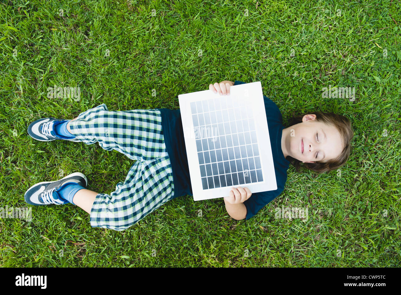 Boy lying on grass holding solar panel - Stock Image