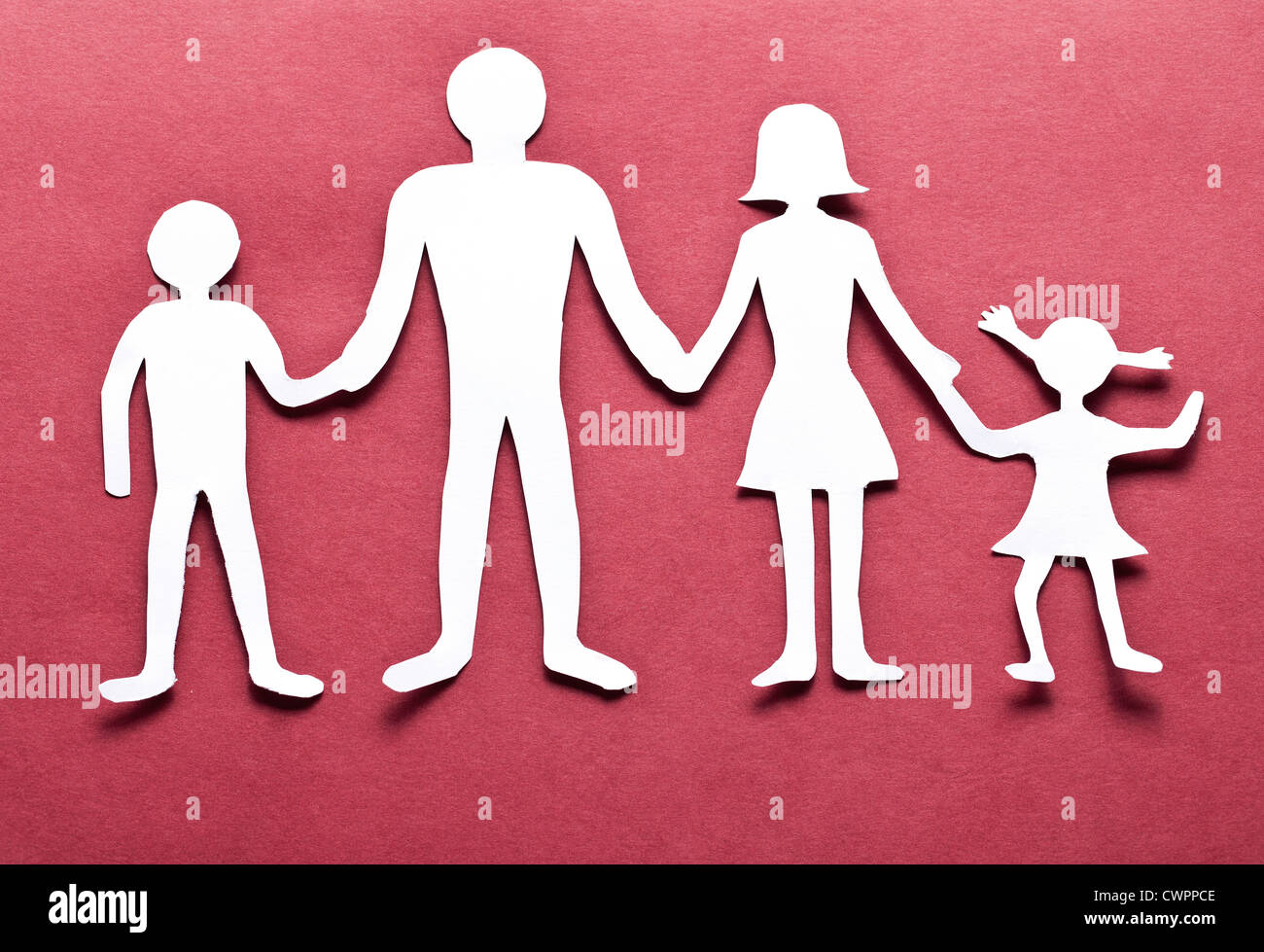 Cardboard Figures Of The Family On A Red Background The Symbol Of