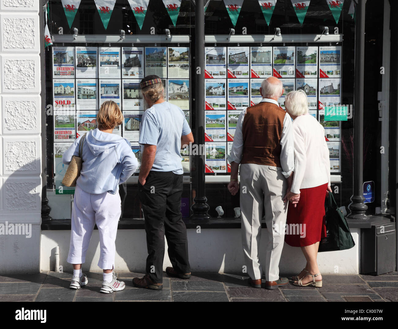 two-couples-one-holding-hands-outside-estate-agents-office-in-caernarfon-CX007W.jpg