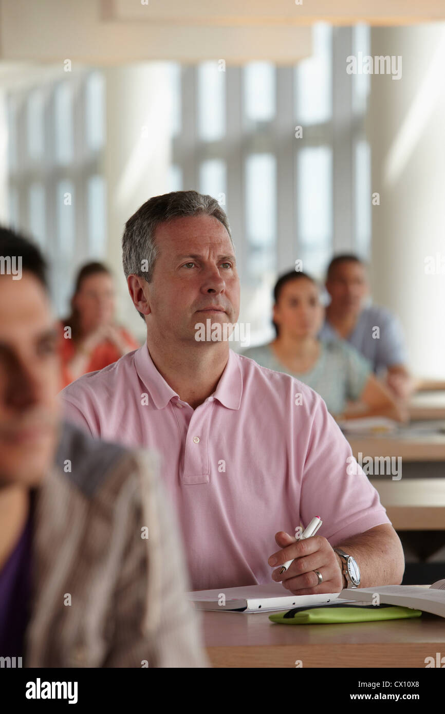 Mature students in class, man making notes - Stock Image