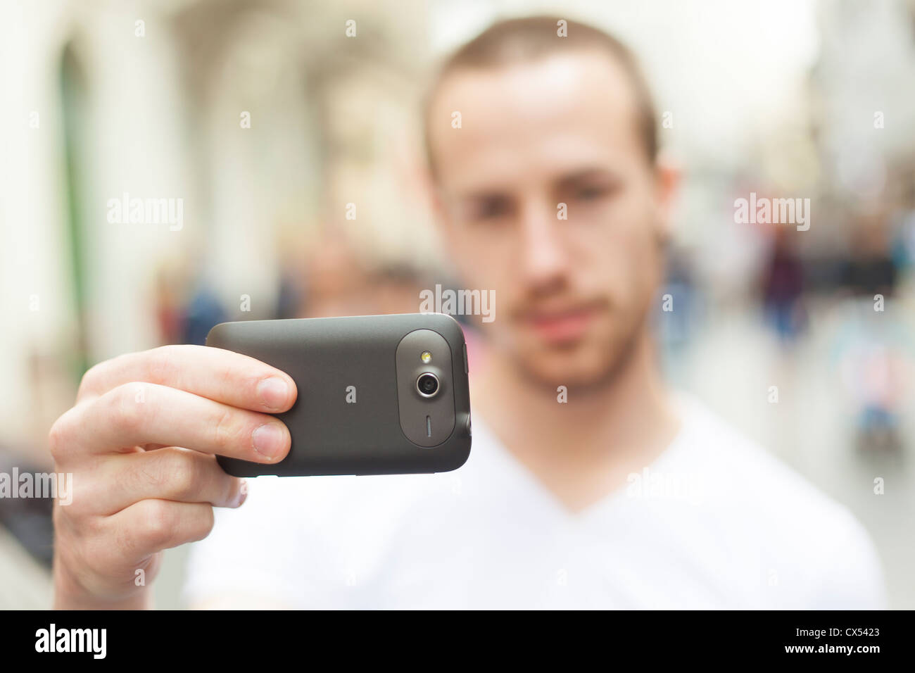 Urban photographer with mobile phone make photo on street - Stock Image