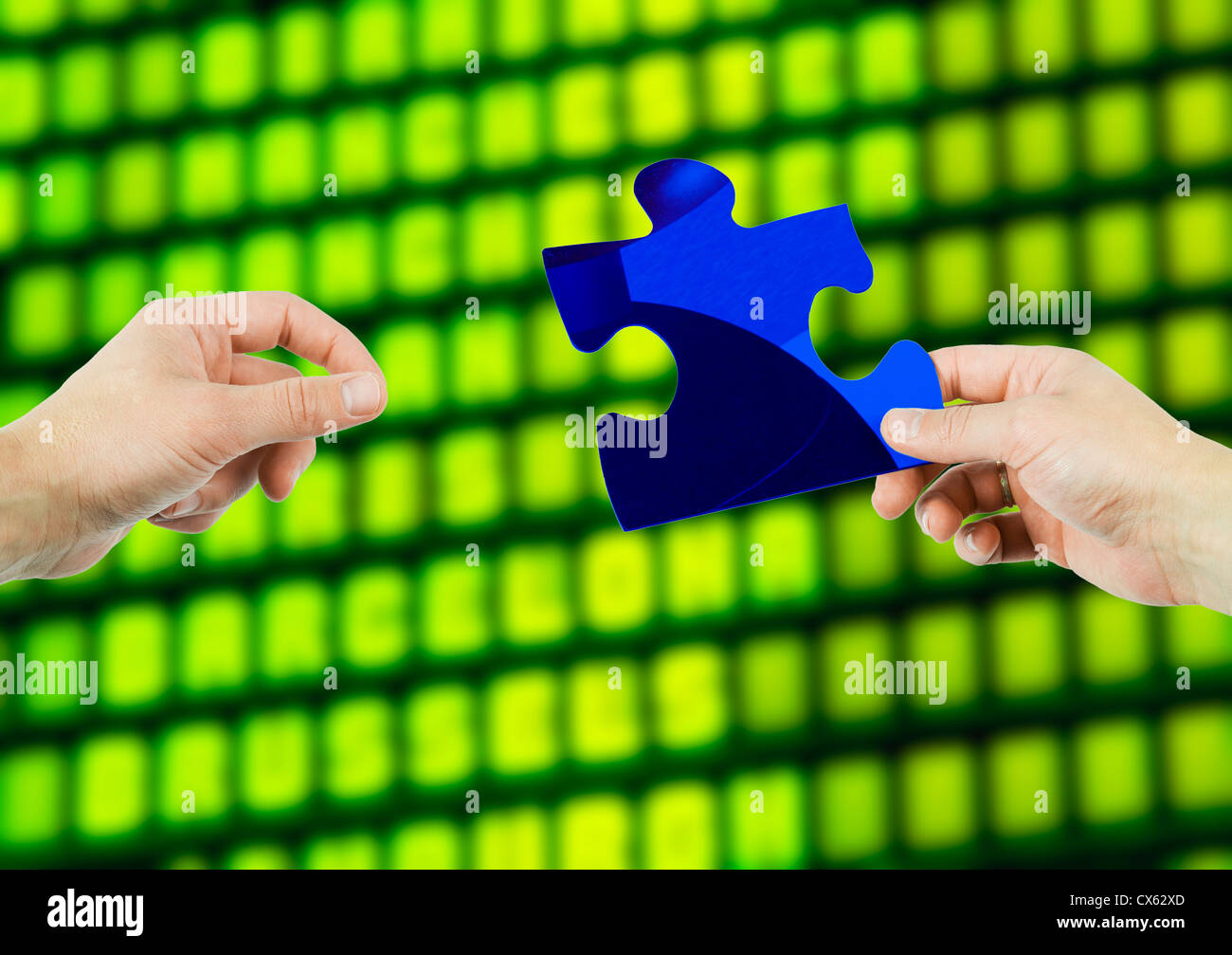 One hand stretching for  piece of a puzzle held by another hand - Stock Image