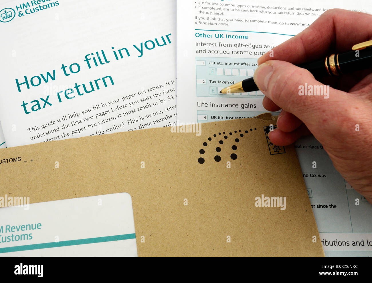 A man filling in an income tax return form, uk Stock Photo