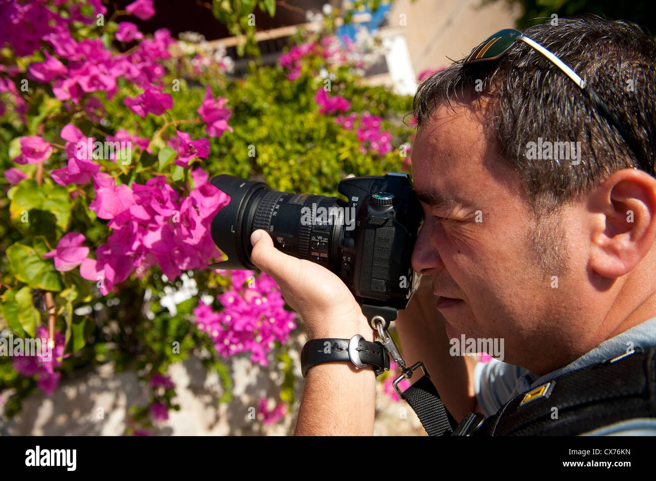 Close up of a photographer using a dslr camera to take a photograph. - Stock Image