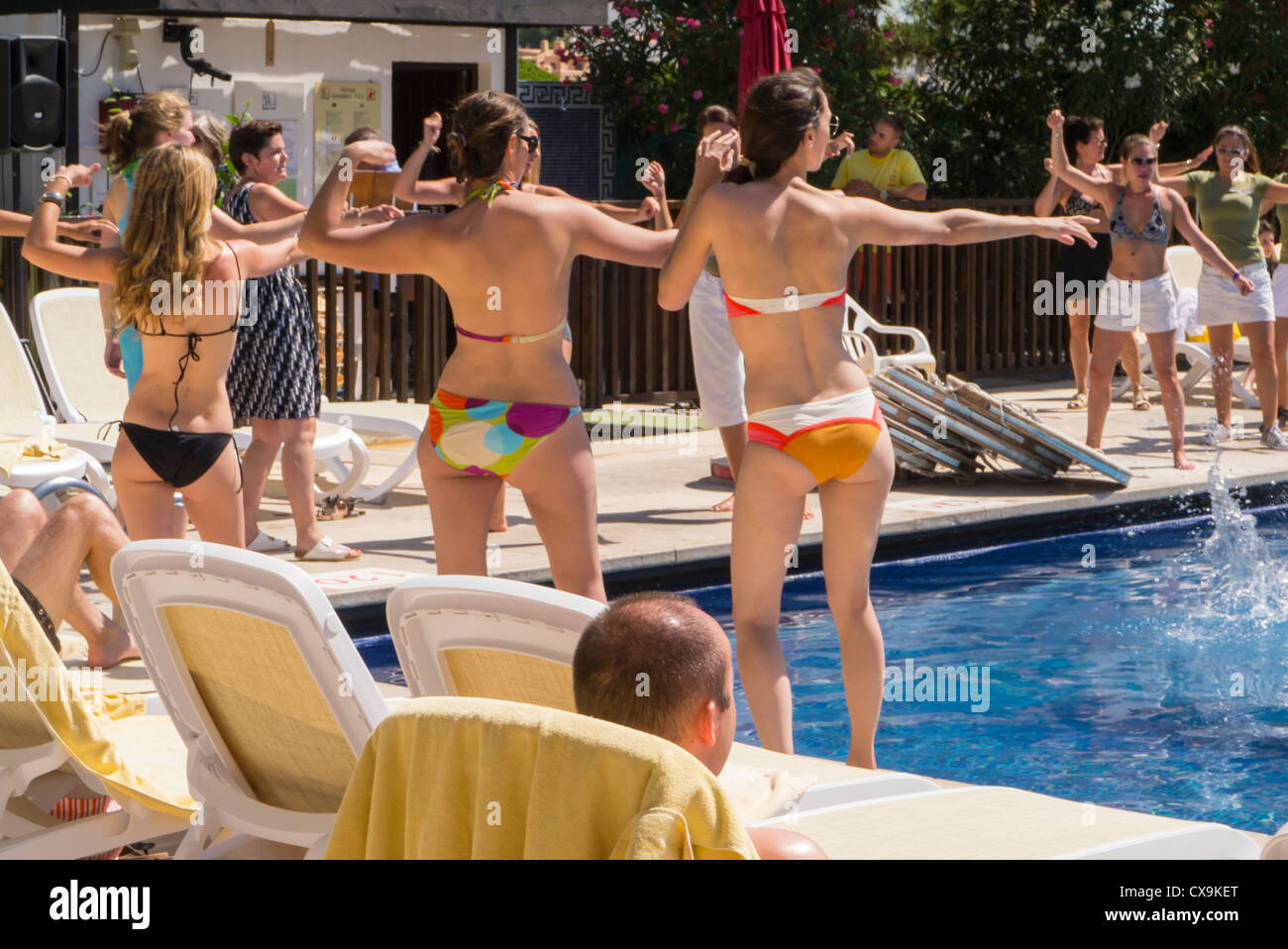 Portugal , Algarve , Club Med , La Balaia , young girls in bikinis doing crazy dance dancing by swimming pool GM - Stock Image