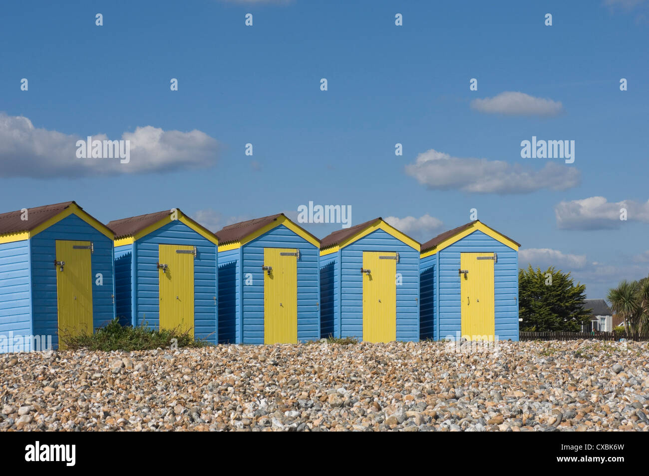 Five blue beach huts with yellow doors, Littlehampton, West Sussex, England, United Kingdom, Europe - Stock Image