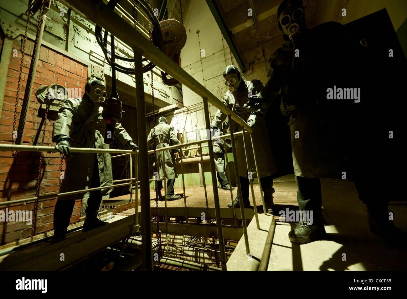 Gas masked menacing men posing in industrial setting - Stock Image
