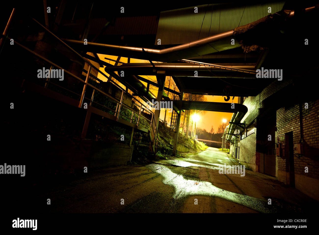 Abandoned industrial site in night after rain - Stock Image
